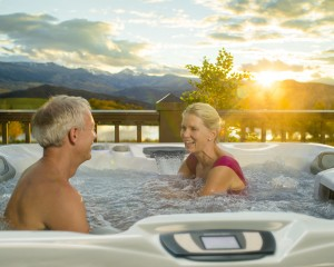 Woman and man spending time in a Sundance Spas hot tub at sunset.