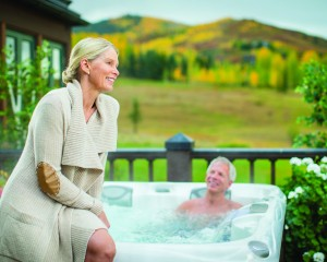 Man soaking in a hot tub and woman sitting on the edge.