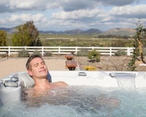 Man soaking in an outdoor hot tub to relieve headache pain.