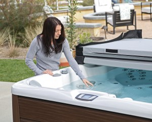 Woman testing the water in her hot tub.