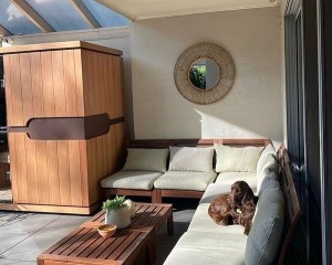Sunlighten Sauna installed in an indoor living space with a sectional couch.